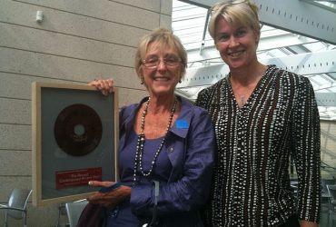 Marilyn Arthur (left) shows off her signed record from artist Satch Hoyt with Kristen Greenaway, former director of development.
