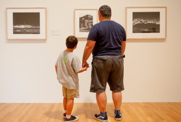 Father and son are holding hands with their backs to the camera and looking at some photographs form the Nasher's collection.
