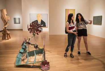 Two Duke student visitors stroll through the gallery near a 1982 painted bronze sculpture, Equipage, by Nancy Graves (center front) and a 1984 portrait of Dr. William G. Anlyan by Alex Katz among others. Photo by J Caldwell.