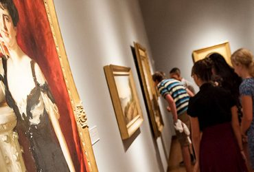 A crowd of museum visitors is seen in the distance perusing several paintings in the Art of the United States Gallery.