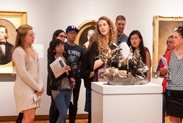 Students stand around a sculpture with a professor all looking at it and engaged in conversation within the Art of the United States Gallery.
