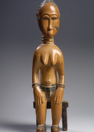This image shows a carved wood very stylized African female figure seated with a large head.