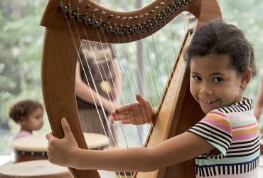 A young visitor plays a stringed instrument during a Free Family Day event. Photo by J Caldwell.