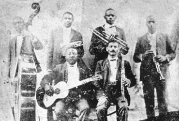 Photo of author Michael Ondaatje and a grainy black-and-white photo of Buddy Bolden and other musicians from the turn of the last century.