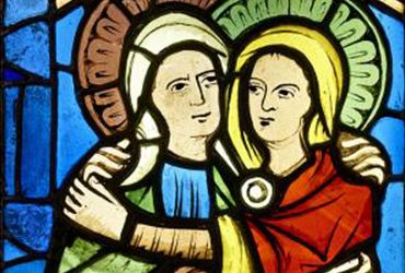 A stained glass image of two figures embracing. They have their faces facing the viewer and very close together. Their arms are wrapped around each other.