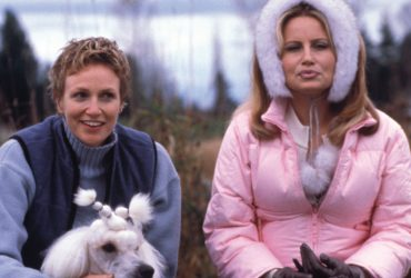 Jane Lynch (left) holds a dog while sitting on a bench with Jennifer Coolidge. Still from Best in Show.