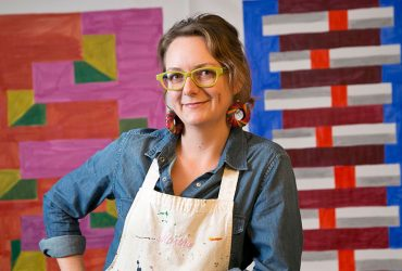 Artist Martha Clippinger poses with right hand on hip, wearing yellow-rimmed glasses, in front of one of her colorful textile works.