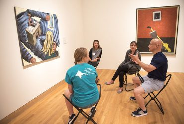Visitors sit on stools in the Disorderly Conduct gallery and focus their attention on a single work of art.