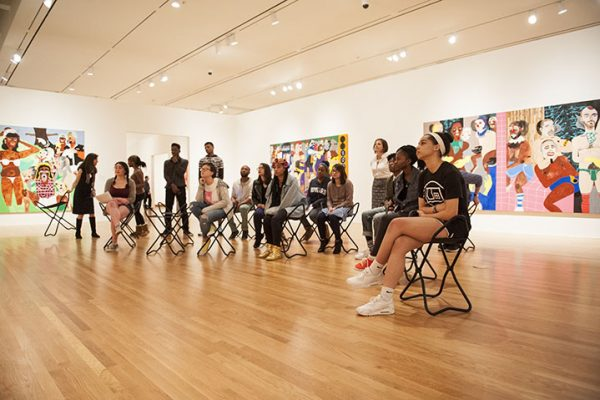 Teens gather in a gallery to talk about works of art.