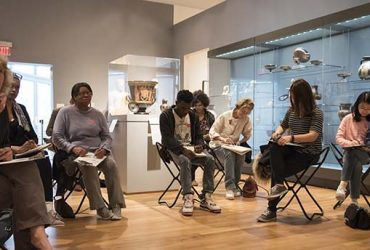 Visitors sit on stools with sketch pads and pencils, drawing works of art around them in the gallery. Photo by J Caldwell.
