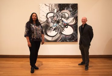 Artist Shinque Smith and curator Marshall Price pose with one of Smith's works in Solidary and Solitary