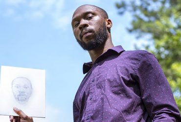Durham artist William Paul Thomas poses with his own sketch, a self portrait. Photo by J Caldwell.