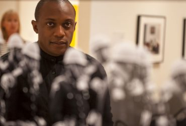 Artist Hank Willis Thomas poses in front of his work, Ain't Gonna Let Nobody Turn Us Around. Photo by J Caldwell.