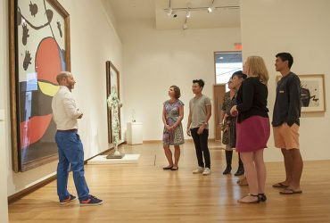 Curator Marshall N. Price (right) leads a tour through Miro: The Experience of Seeing. Photo by J Caldwell.