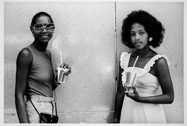 A black-and-white photograph depicts two black women holding paper cups with lids and straws. The woman on the left is smiling in sunglasses; the woman on the right is gazing solemnly. She is wearing a white sundress.