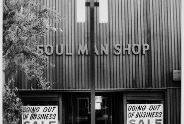 "A black-and-white photograph depicts the facade of a building with ""going out of business"" signs in the windows."