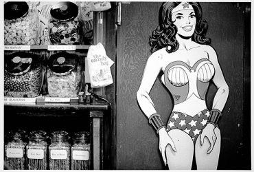 A photo from a street vendor's cart or a small shop features a full-size cutout of the cartoon Wonder Woman with hands on hips.