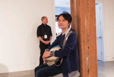 "Nasher artist Taiyo Kimura (pictured) sits on one of his own sculptures, ""Untitled (Stool for Guard),"" on view at the Contemporary Arts Center. Photo by J Caldwell."