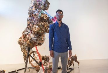 "P.4 artist Lavar Munroe poses in front of his sculpture, ""Of the Omens He Had as He Entered His Own Village, and Other Incidents That Embellished and Gave Color to a Great History,"" at the Contemporary Arts Center. Photo by J Caldwell."