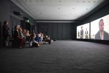 "A crowd at the Ogden Museum takes in John Akomfrah's much-anticipated three-channel video, ""Precarity."" This video will be one of the Nasher Museum's major spring 2018 exhibitions. The Nasher Museum co-commissioned the new work, thanks to the generosity of Nancy A. Nasher and David J. Haemisegger. Photo by J Caldwell."