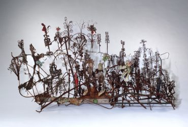 Thornton Dial, Monument to the Minds of the Little Negro Steelworkers, 2001–2003. Steel, wood, wire, twine, artificial flowers, ax blade, glass bottles, animal bones, cloth, tin cans, paint-can lids, and enamel; 38 x 76 x 46 inches (96.5 x 193 x 116.8 cm). Courtesy of the artist and William S. Arnett Collection of the Souls Grown Deep Foundation, Atlanta, Georgia. © Estate of Thornton Dial. Photo by Stephen Pitkin.