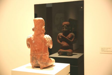 Pedro Lasch, Black Mirror #4: Hypnotism & Necromancy, 2008. Installation using Jalisco, Mexico, Ameca Gray type, Seated female figure, 200 BCE- 300 CE, ceramic with red and gray-white slip paint. Collection of the Nasher Museum, from the Paul A. and Virginia Clifford Collection. Reproduction behind glass: El Greco, Portrait of an Ecclesiastic, about 1610-14. Oil on canvas, 42 1/8 x 35 1/2 inches. Collection of the Kimbell Art Museum, Fort Worth, Texas.
