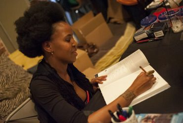 Wangechi Mutu signs a book at Motorco Music Hall, where the Nasher Museum hosted an artist talk, catalogue signing and dance party. Photo by J Caldwell.