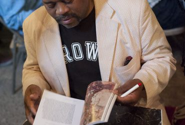 Music critic Greg Tate signs a catalogue at Motorco Music Hall. Photo by J Caldwell.