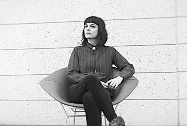 Black-and-white photo of Casey Cook sitting in a chair, a still from the video by J Caldwell.