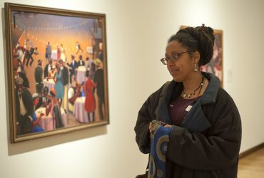 A visitor is deeply engrossed in Archibald Motley: Jazz Age Modernist. Photo by J Caldwell.