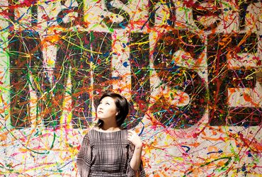 Duke student, Young Kim, poses in front of a Nasher MUSE banner at a MUSE party at the museum.