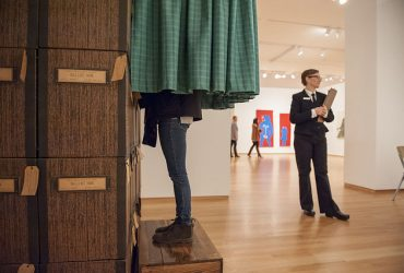 A visitors' legs peek out from under the green curtain of Stacey L. Kirby's Power of the Ballot. The artist stands nearby with a clipboard.