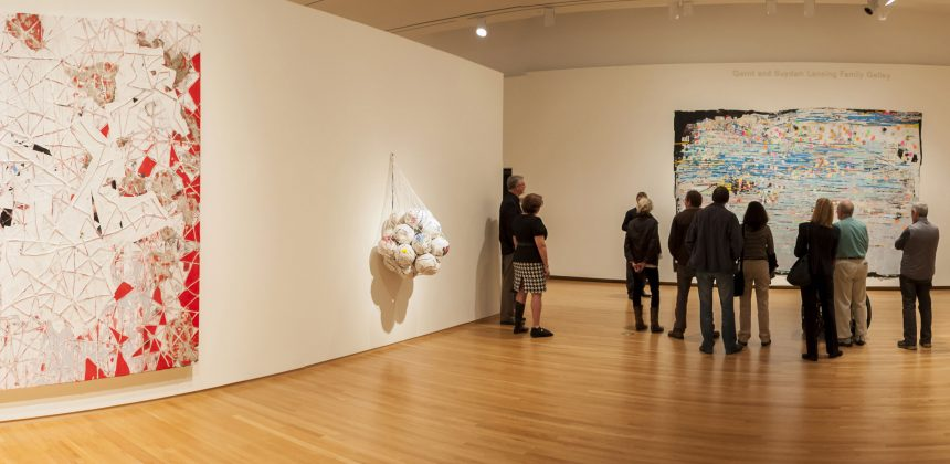 Visitors tour an installation of Mark Bradford's work, including his mixed media work Red Painting, Soccer Ball Bag 4 and Potable Water with Trevor Schoonmaker, Chief Curator and Patsy R. and Raymond D. Nasher Curator of Contemporary Art. Photo by J Caldwell.