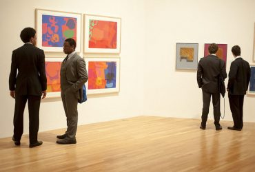 Visitors enjoy Colour Correction: British and American Screenprints, 1967-75 . This photo shows four full-length male figures pausing in a gallery with six colorful prints on the wall.