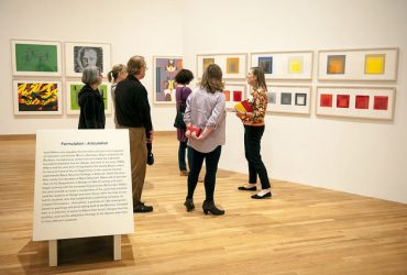 Gallery Guide Ruth Caccavale (right) leads a group of five visitors through Colour Correction: British and American Screenprints, 1967-75 . Photo by J Caldwell.