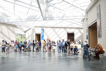 Visitors crowd the Great Hall during Miró: The Experience of Seeing. Families have lined up for a poem by the Poetry Fox (right). Photo by J Caldwell.