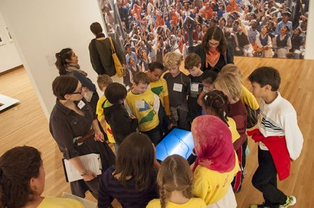 Young visitors lean in for a closer look at a video of an ant caught within a drawn line. The 2013 video was created by Bengaluru artist Surekha, entitled Line of Control. Photo by J Caldwell.