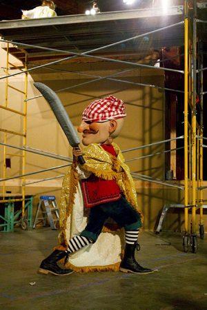A full figure dressed as a pirate raises a sword.