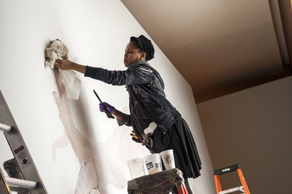 Wangechi Mutu works on a monumental entrance wall drawing, Once upon a time she said, I'm not afraid and her enemies became afraid of her The End. Photo by J Caldwell.