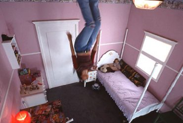 In this still from the video Pink Constellation, a female figure seems to float upside-down in a bedroom with pink walls.
