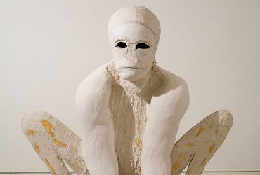 A figure made of white plaster with black holes for eyes squats with knees bent and hands flat on the floor.