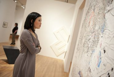 A visitor takes a look at a work by Mark Bradford in the exhibition Open This End. Photo by J Caldwell.