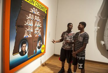 Duke students take a close look at a work by Roger Brown, Kissin' Cousins. Photo by J Caldwell.