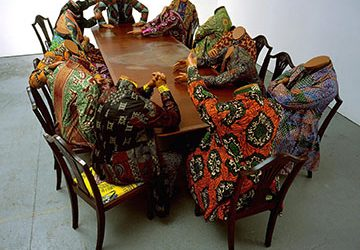 Yinka Shonibare, Scramble for Africa, 2003. Fourteen life-size fiberglass mannequins, fourteen chairs, table, and Dutch wax printed cotton; overall: 52 x 192 1/8 x 110 1/4 inches (132.1 x 488 x 280 cm). The Pinnell Collection, Dallas, Texas. © Yinka Shonibare MBE. All Rights Reserved, DACS 2013.