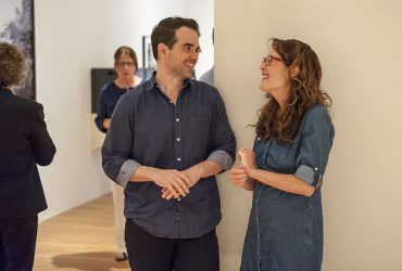 Artist Dario Robleto (left) chats with co-curator Miranda Lash at the exhibition opening. Photo by J Caldwell.
