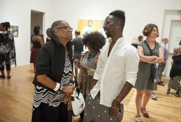Artist Fahamu Pecou (right) chats with a visitor during the opening event. Photo by J Caldwell.