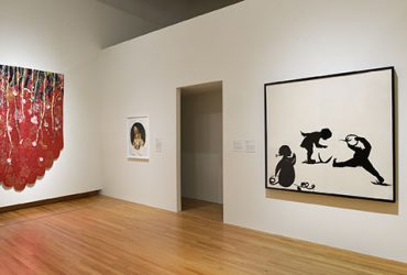 Gallery installation view, featuring a work by Ebony G. Patterson, Strange Fruitz, on the left and a work on paper by Kara Walker on the right, Cottonhead, a Mouthful of Teeth and Spitting Seeds. Photo by Peter Paul Geoffrion.