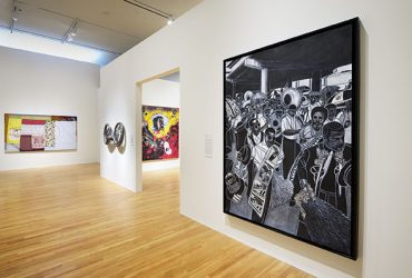 Gallery installation view, featuring a work (right wall) by Willie Birch. Photo by Peter Paul Geoffrion.
