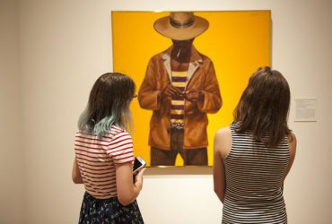 Two visitors take a close look at a painting by Barkley L. Hendricks. Photo by J Caldwell.