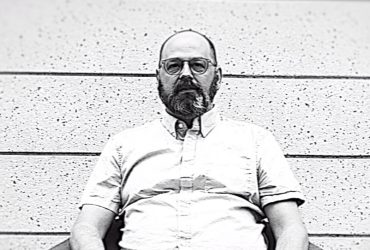 Black-and-white photo of Bill Thelen, seated in a chair, a still from the video by J Caldwell